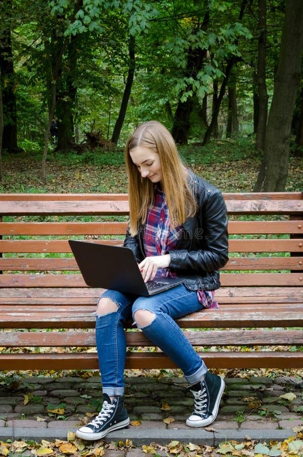 Jovem mulher de sorriso que trabalha com um portátil fotos de stock royalty free