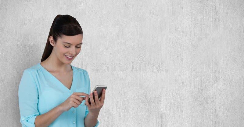 Jovem mulher de sorriso que usa o telefone celular foto de stock
