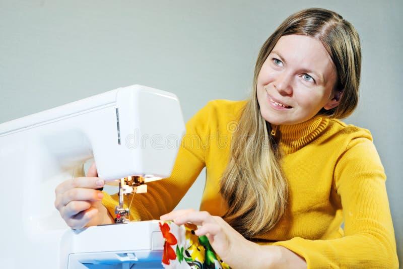 Mulher que usa uma máquina de costura imagens de stock royalty free