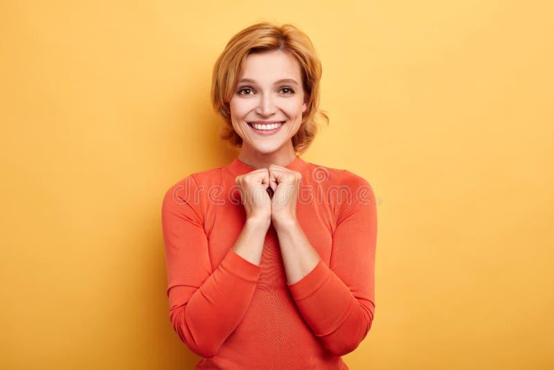 Jovem mulher de sorriso romântica calma que mantém as mãos unidas no punho imagem de stock