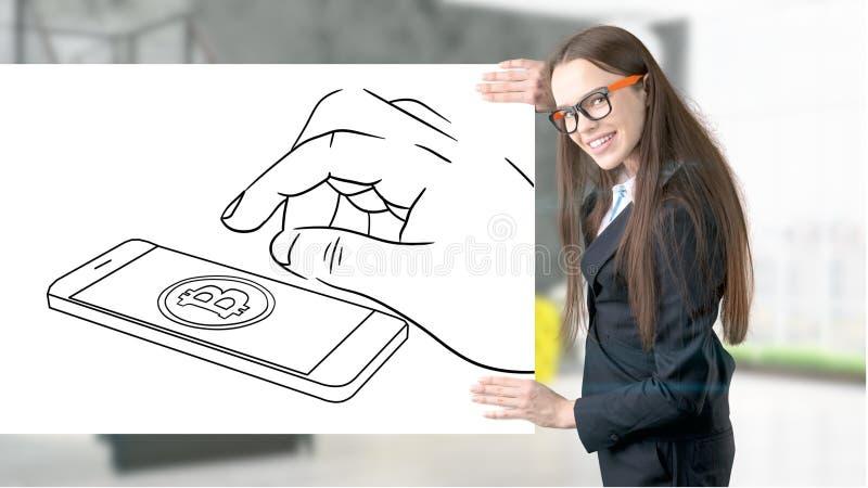 Jovem mulher de sorriso Surprised que veste um terno e que olha um esboço do cryptocurrency em uma parede lisa do projeto Conceit foto de stock