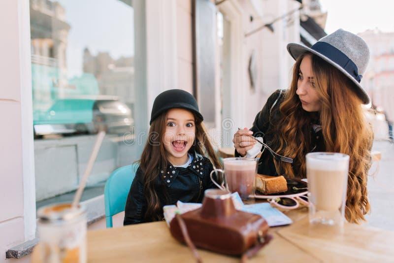 Jovem mulher de surpresa no chapéu cinzento do vintage que come o bolo de queijo saboroso com sua irmã mais nova no fim de semana foto de stock