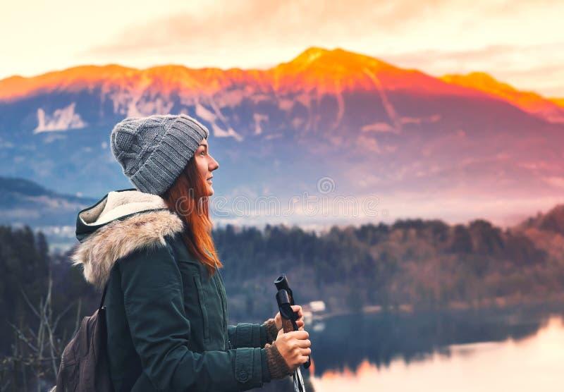 Jovem mulher de viagem que olha no por do sol no lago Bled, Eslovênia, fotografia de stock