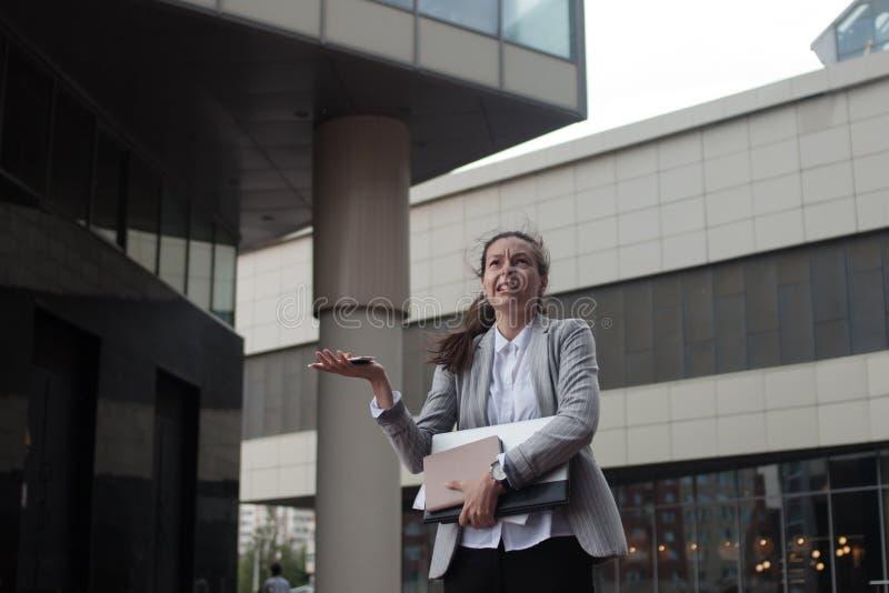 A jovem mulher decepcionada é uma mulher de negócios, estando no fundo do centro de negócios fotografia de stock royalty free