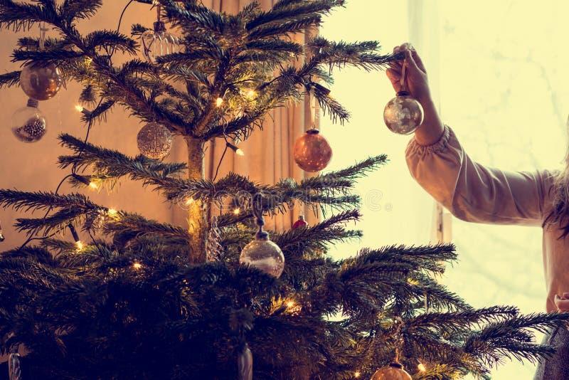 A jovem mulher decora uma árvore de Natal, feriado da tradição imagens de stock royalty free