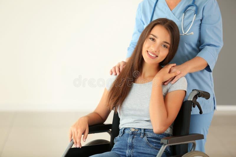 Jovem mulher deficiente com o doutor fêmea maduro na clínica imagem de stock