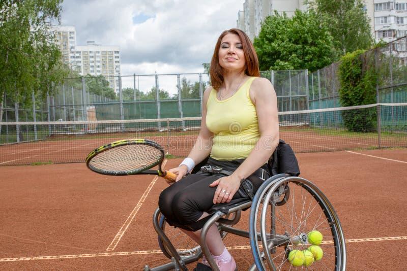 Jovem mulher deficiente na cadeira de rodas que joga o tênis no campo de tênis fotos de stock