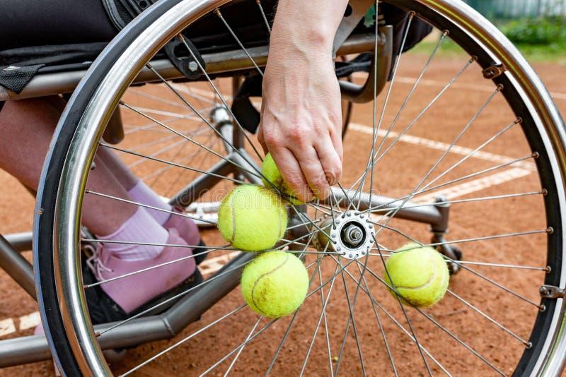 Jovem mulher deficiente na cadeira de rodas que joga o tênis no campo de tênis O close-up de uma mão toma uma bola de tênis fixad imagem de stock royalty free