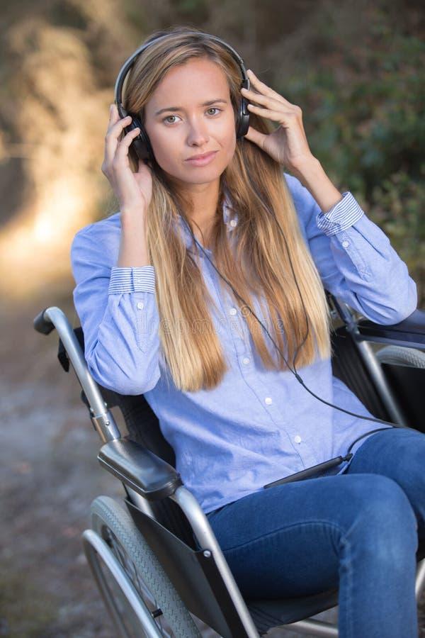 Jovem mulher deficiente no ar livre da cadeira de rodas na cena rural imagem de stock