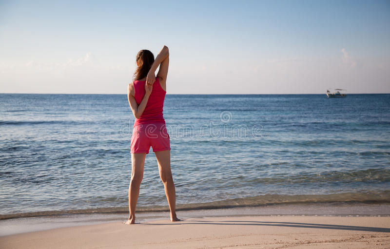 Jovem mulher delgada que faz exercícios na costa de mar imagem de stock