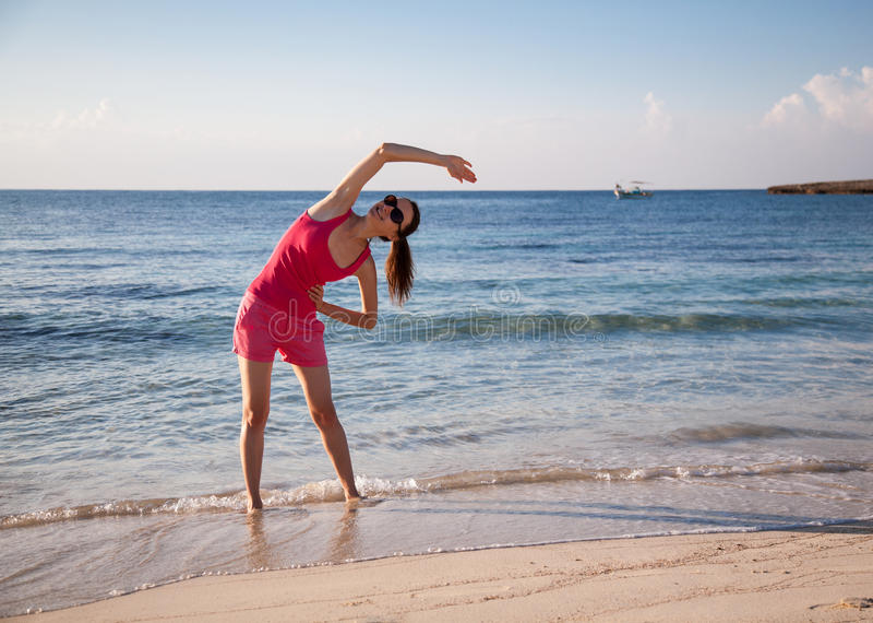 Jovem mulher delgada que faz exercícios na costa de mar foto de stock