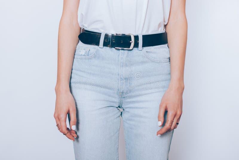 Jovem mulher delgada que veste calças de brim altas azuis da cintura fotos de stock