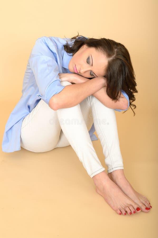 Jovem mulher deprimida e irritada triste bonita que senta-se no Flo imagem de stock royalty free
