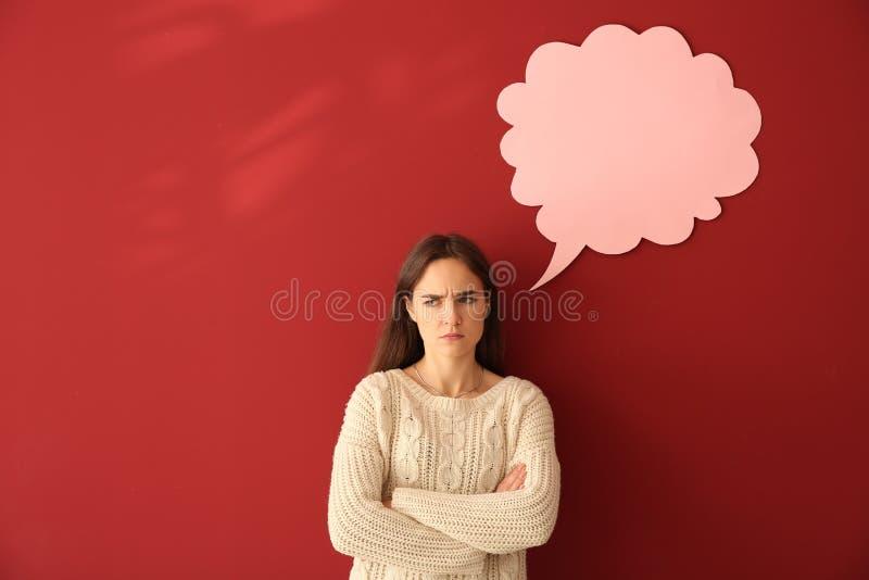 Jovem mulher desagradada perto da bolha vazia do discurso no fundo da cor fotografia de stock