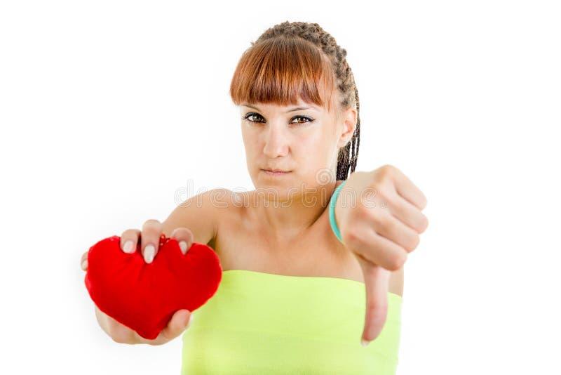 Jovem mulher desapontado que guarda tristemente o coração que mostra o polegar para baixo foto de stock