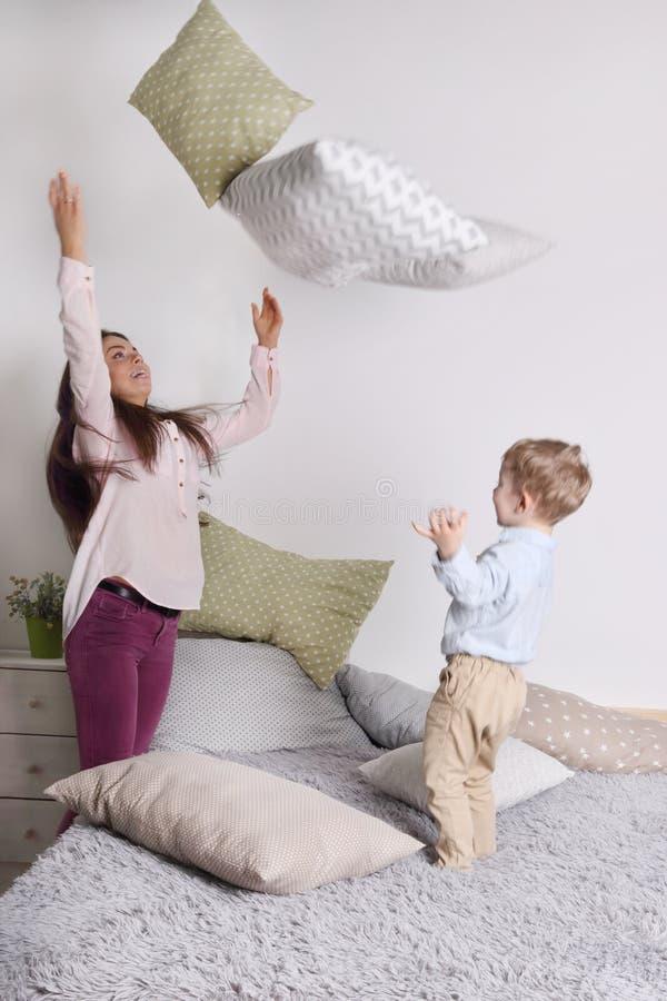 Jovem mulher, descansos de lance pequenos do filho na cama cinzenta imagens de stock