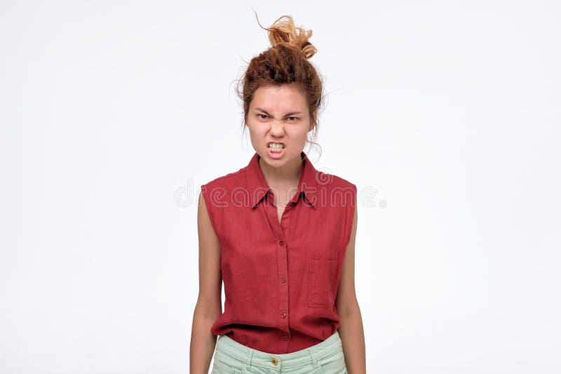 Jovem mulher descontentada que faz caretas, apertando os dentes e fazendo o gestur irritado fotos de stock royalty free