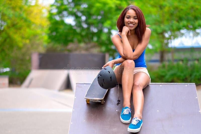 Jovem mulher desportiva com um skate imagens de stock