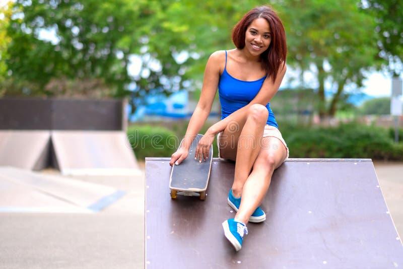 Jovem mulher desportiva com um skate imagem de stock royalty free