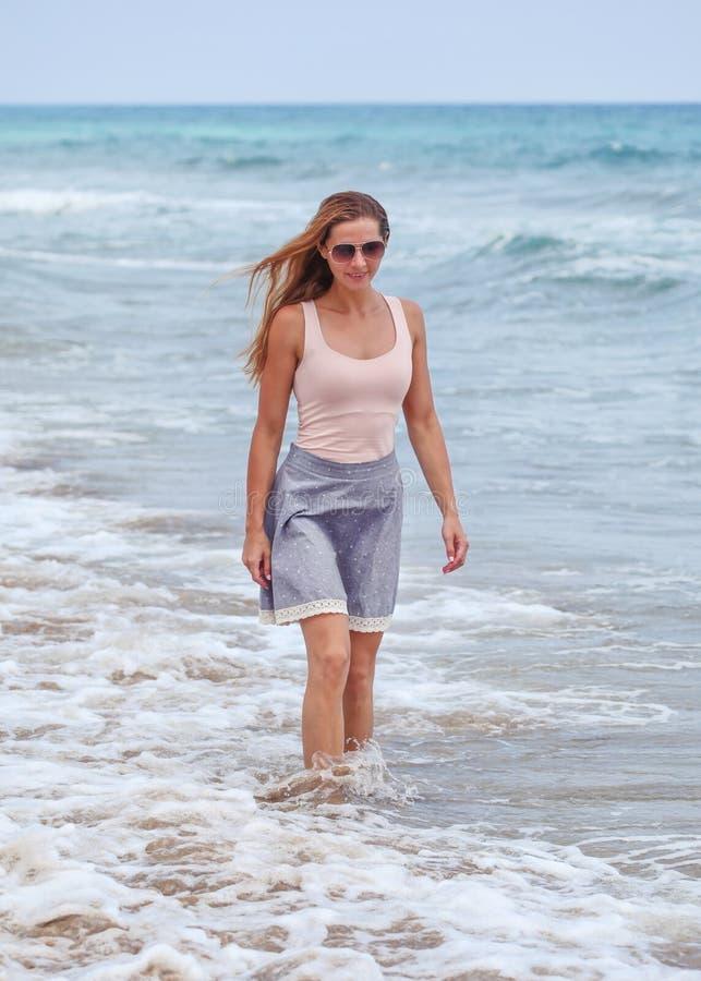 Jovem mulher desportiva na saia, as camisas de t e os óculos de sol estando no mar raso, ondas pequenas e céu nublado atrás dela foto de stock royalty free