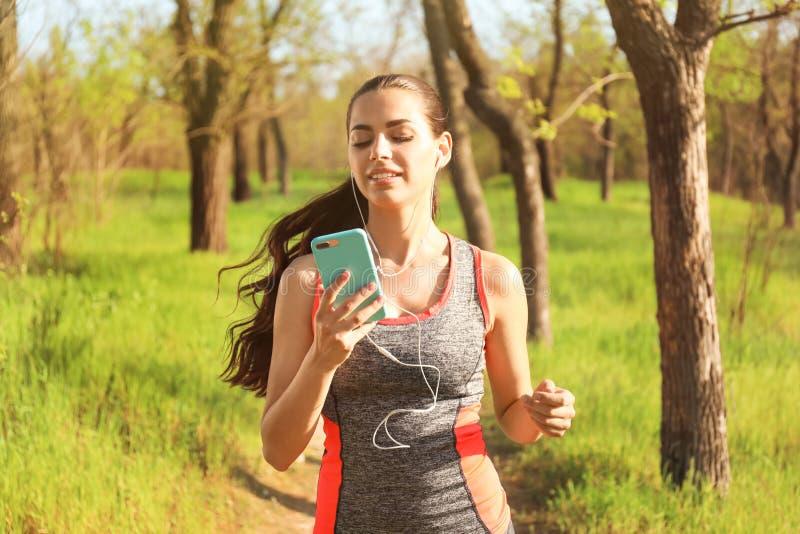 Jovem mulher desportiva que escuta a música ao correr no parque fotografia de stock royalty free