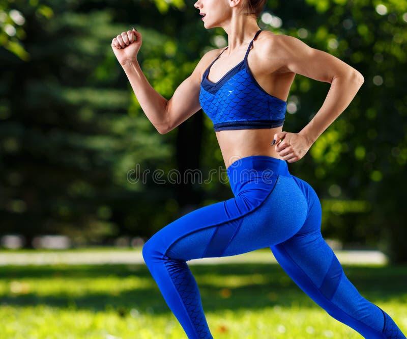 Jovem mulher desportiva que movimenta-se fora no ver?o fotos de stock
