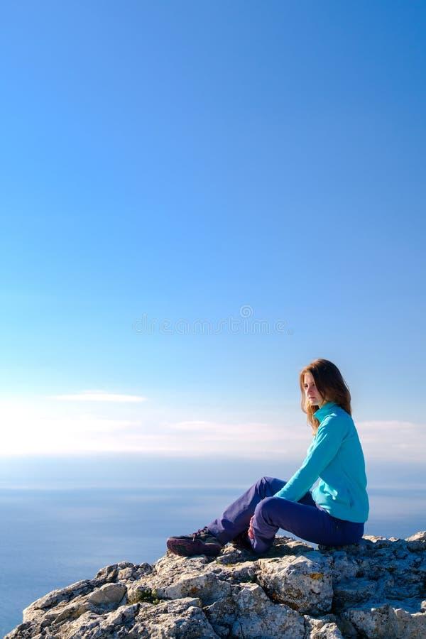 Jovem mulher desportiva que senta-se em uma parte superior rochosa da montanha contra o azul do céu e do mar fotos de stock