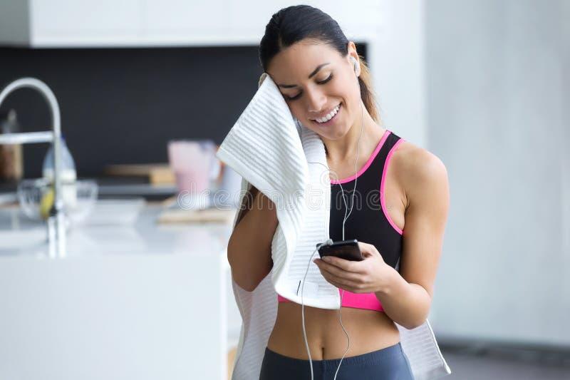 Jovem mulher desportiva que usa seu telefone celular ao secar o suor com uma toalha em casa fotos de stock