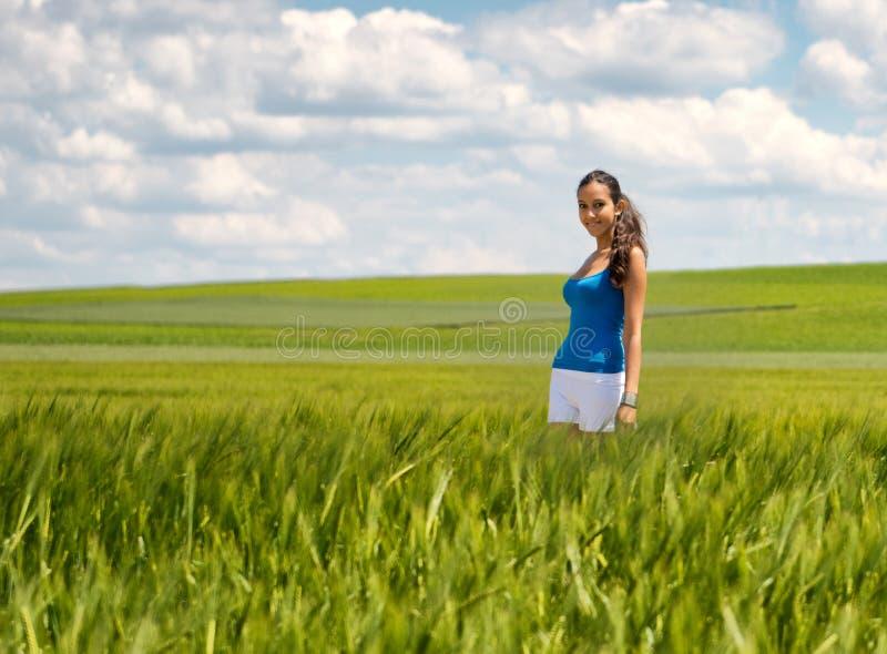 Jovem mulher despreocupada feliz em um campo de trigo verde foto de stock