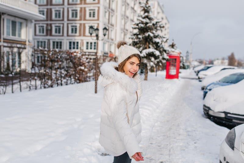A jovem mulher despreocupada no chapéu feito malha vai ao carro no dia e no riso de inverno Foto exterior da menina de sorriso bo fotos de stock royalty free