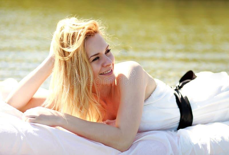 Jovem mulher despreocupada que relaxa na cama fora na água imagem de stock