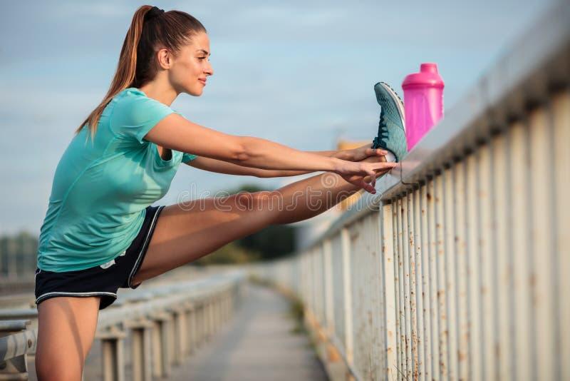 Jovem mulher determinada que estica os pés após um exercício urbano exterior duro imagem de stock