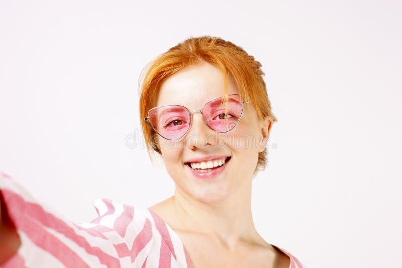 Jovem mulher dirigida vermelha bonita que levanta, mostrando expressões faciais emocionais e fazendo as caras engraçadas com tele imagem de stock