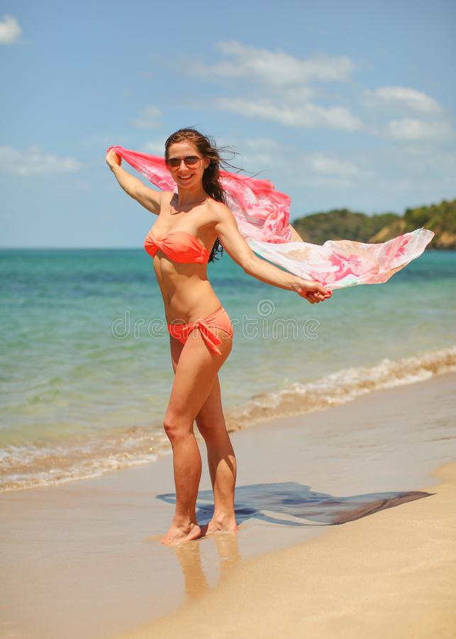 Jovem mulher do ajuste no biquini e nos óculos de sol vermelhos, suportes na praia, guardando o lenço cor-de-rosa que acena no ve foto de stock royalty free