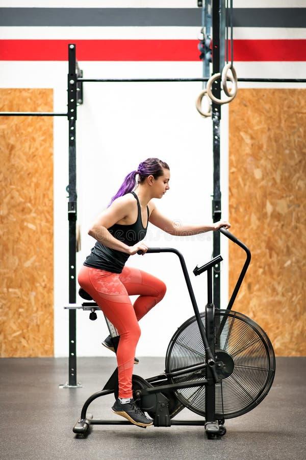 Jovem mulher do ajuste que dá certo em uma bicicleta de exercício imagem de stock royalty free