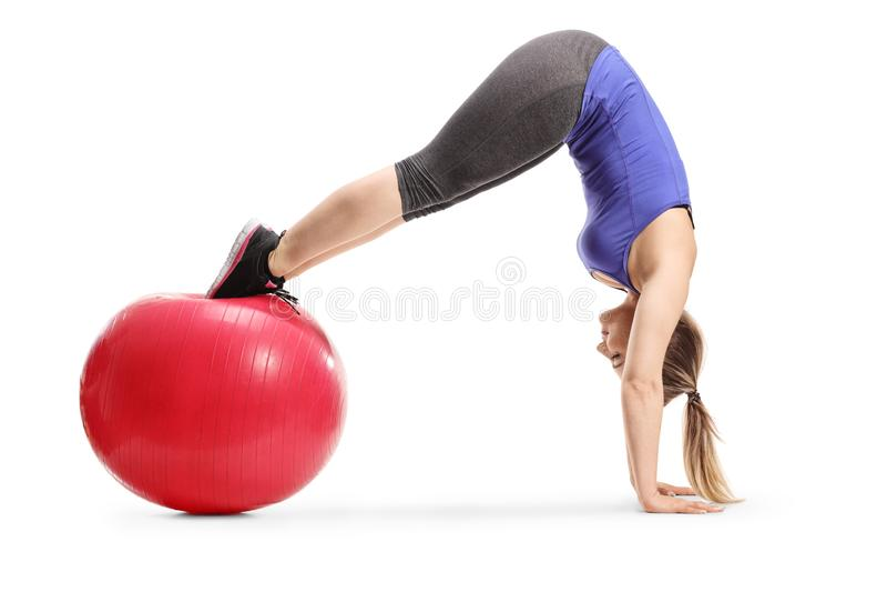 Jovem mulher do ajuste que equilibra em uma bola da aptidão e em um pino praticando fotografia de stock