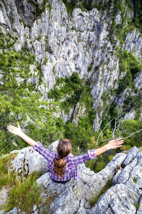 Jovem mulher do caminhante que estica seus braços na montanha fotos de stock