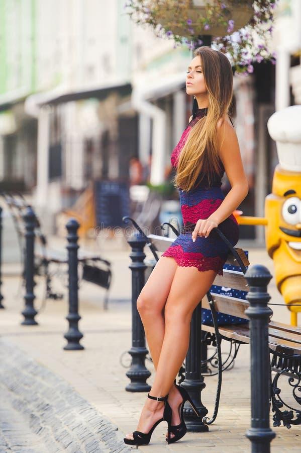 Jovem mulher do encanto da beleza em uma cidade acolhedor inclinou seus cotovelos no banco Cabelo longo Senhora elegante com um p imagem de stock royalty free