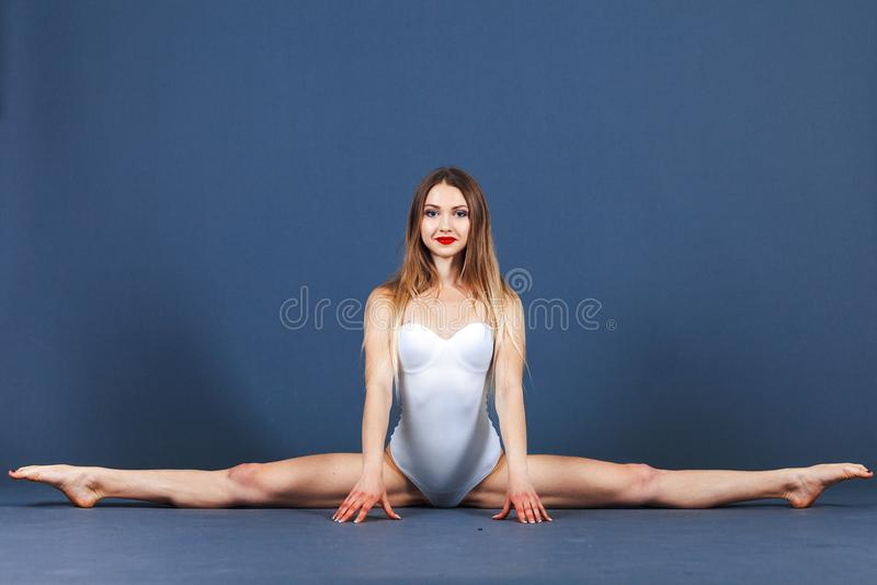 A jovem mulher do esporte no bodysuit do sportwear senta-se em uma guita em um fundo azul Tiro do estúdio fotos de stock royalty free
