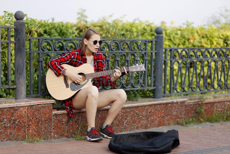 Jovem mulher do músico da rua que joga a guitarra acústica e que canta em um parque da cidade foto de stock royalty free