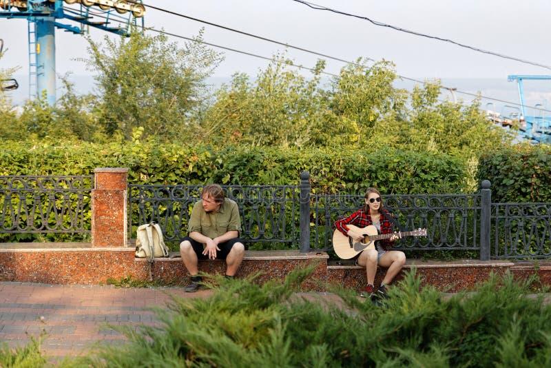 Jovem mulher do músico da rua que joga a guitarra acústica e que canta em um parque da cidade imagem de stock