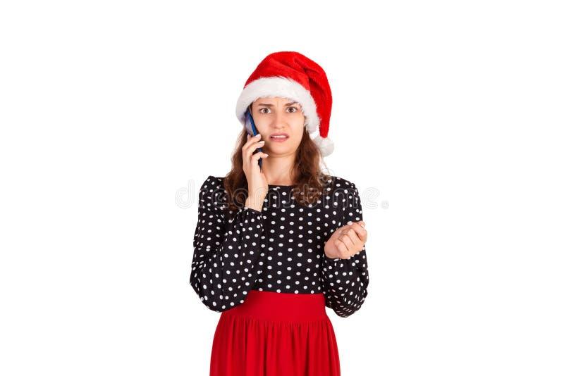 Jovem mulher do retrato do close up, comprimida, a triste e preocupada que fala no telefone menina emocional no chapéu do Natal d imagens de stock