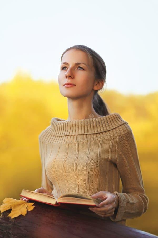 A jovem mulher do retrato com livro e a folha de bordo amarela sonha fora no outono ensolarado morno imagens de stock