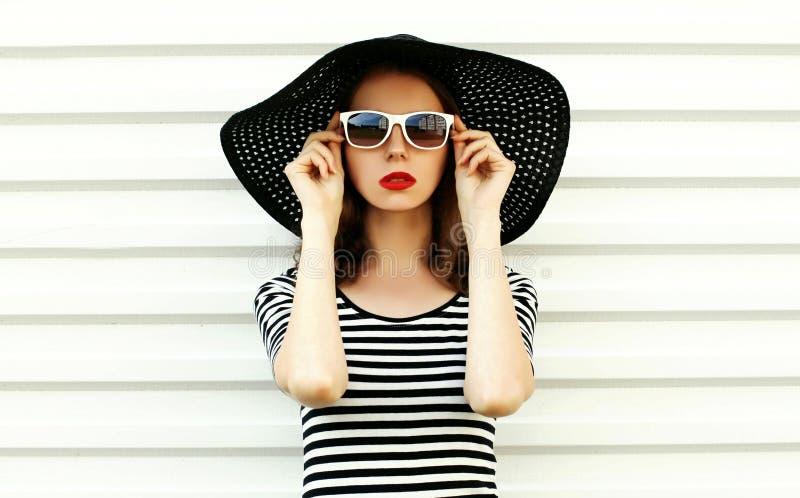 Jovem mulher do retrato da forma no chapéu de palha preto do verão que levanta na parede branca imagens de stock royalty free