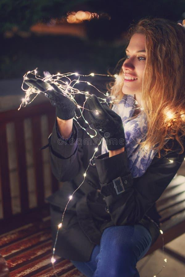 Jovem mulher do ruivo que guarda luzes feericamente no parque no inverno imagem de stock royalty free