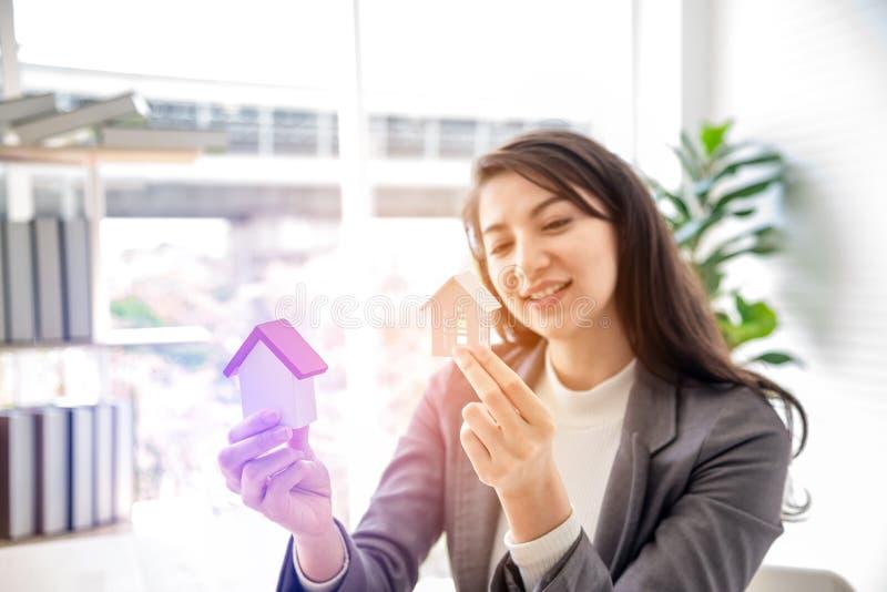 A jovem mulher do smiley da felicidade que guarda duas casas de madeira pequenas do modelo modela nas mãos Escolha do seguro pat imagem de stock royalty free