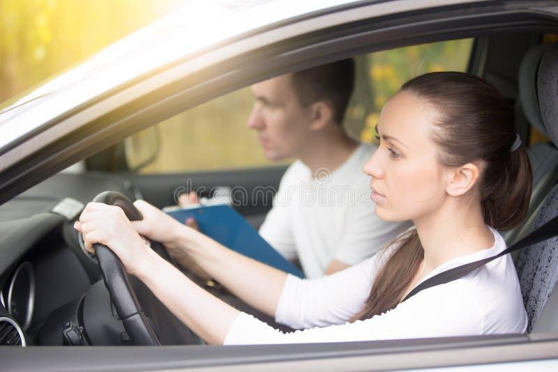Jovem mulher do teste de condução que conduz um carro, homem que senta-se de lado fotografia de stock