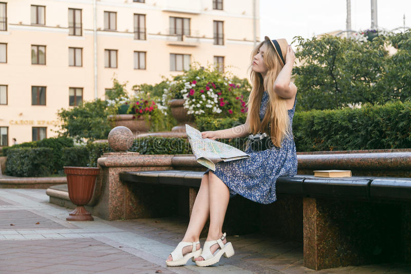 Jovem mulher do turista que senta-se no banco que olha o mapa imagem de stock royalty free