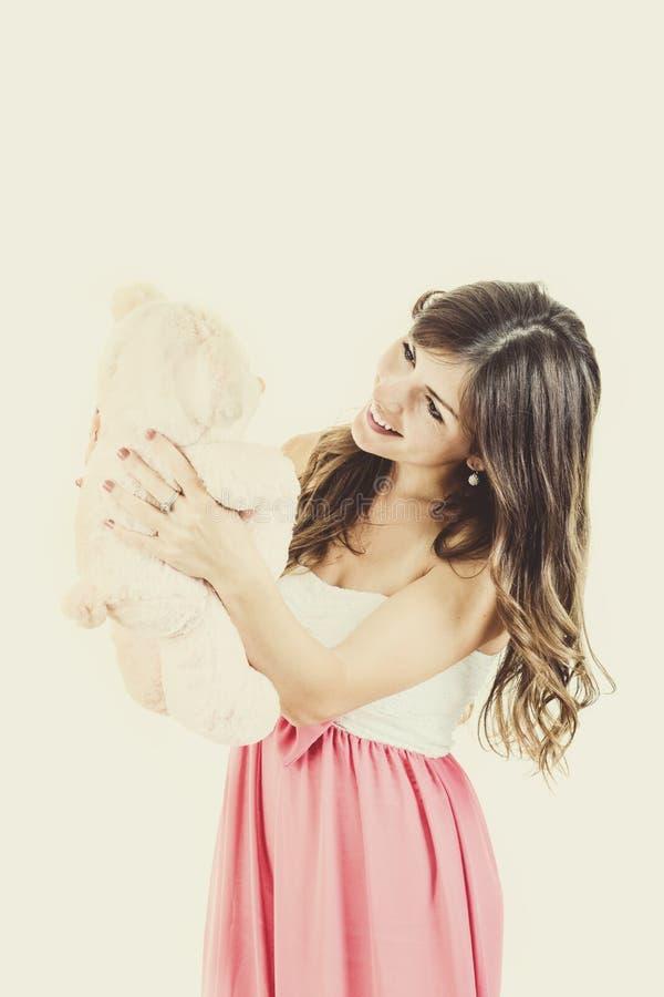 Jovem mulher doce que guarda o sorriso do urso de peluche imagens de stock royalty free