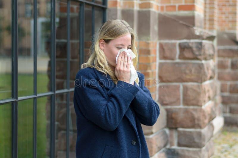 Jovem mulher doente que funde seu nariz foto de stock
